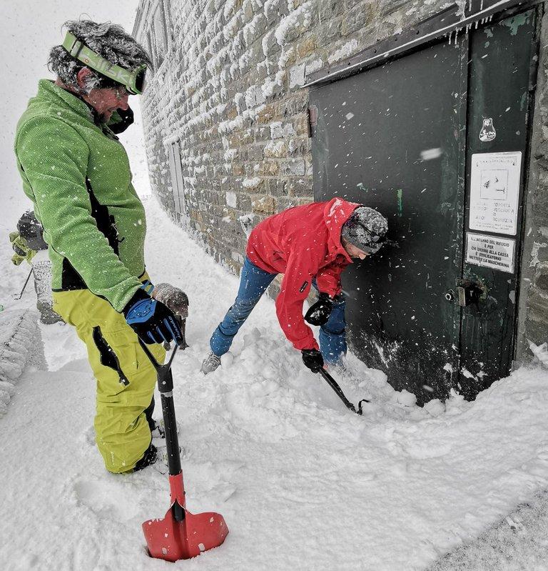 apertura porta del rifugio con la neve